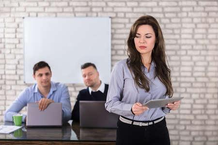 若い実業家のオフィスで 2 つのビジネスマンの前にデジタル タブレットを保持 写真素材 - 83019518