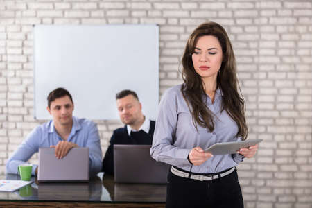 Young Businesswoman Holding Digital Tablet In Front Of Two Businessman In Office