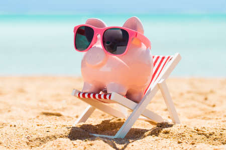 Pink Piggy Bank With Sunglasses On The Small Deck Chair At Beach
