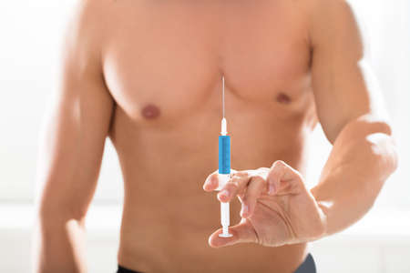 steroid: Close-up Of A Shirtless Bodybuilder Man Holding Syringe In His Hand Against Black Background