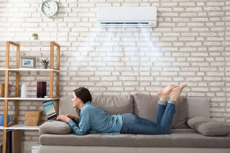 Woman Lying On Sofa Using Laptop Enjoying The Cooling Of Air Conditioner At Home 스톡 콘텐츠