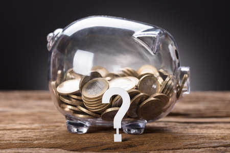 Closeup of question mark and coins in transparent piggy bank on table Stock Photo