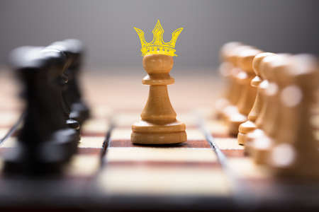 Closeup of pawn with king crown amidst chess pieces on board game representing leadership