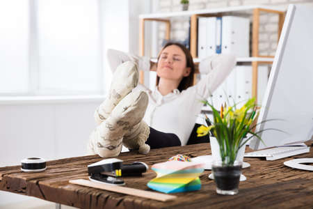 Young Businesswoman Wearing Socks Sleeping At Workplace