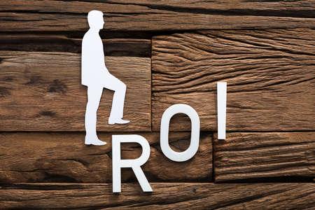 Closeup of paper businessman climbing ROI ladder on wood