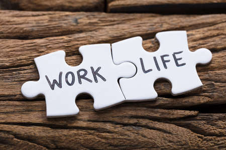 Closeup of work and life words written on pieces of jigsaw puzzle against wood