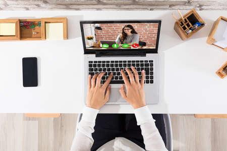 職場のラップトップ上で幸せな女実業家ビデオ会議の昇格を表示 写真素材