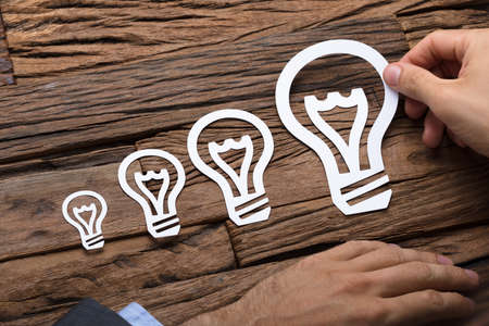 Cropped image of businessman arranging paper light bulbs in increasing order on wooden table Stock Photo
