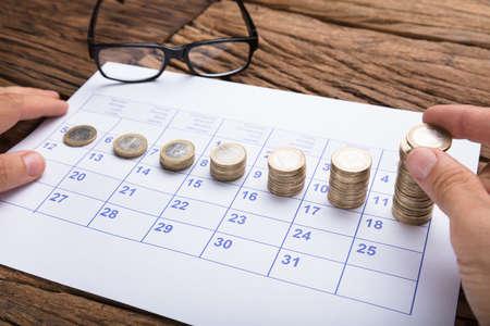 カレンダー順に実業家スタッキング コインのトリミングの手 写真素材