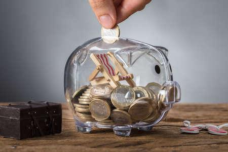 Close-up van hand die muntstuk in transparant spaarvarken met ligstoel zetten