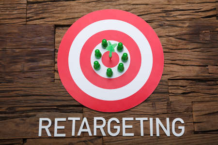 Arrow and pawn figurines on dartboard with retargeting text at wooden table