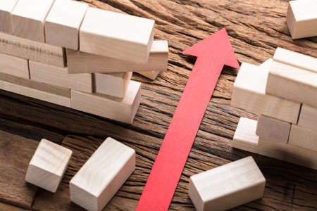 High angle view of red paper arrow amidst blocks on wooden table