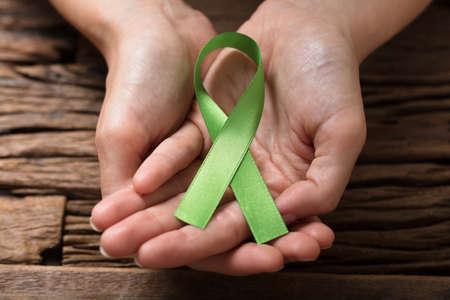 Menselijke hand die groen lint toont om orgaantransplatbewustzijn te ondersteunen Stockfoto - 82978749