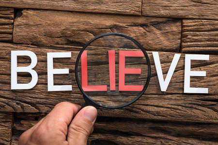 Closeup of hand holding magnifying glass over word lie in believe on wood