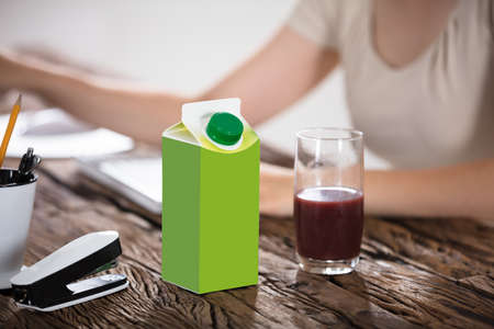 Juice Package And Juice Glass On Wooden Table