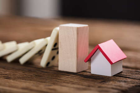Closeup of wooden block amidst model house and domino pieces representing home insurance on table Foto de archivo