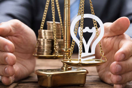 Businessman covering paper light bulb and coins on golden weighing scale at wooden table
