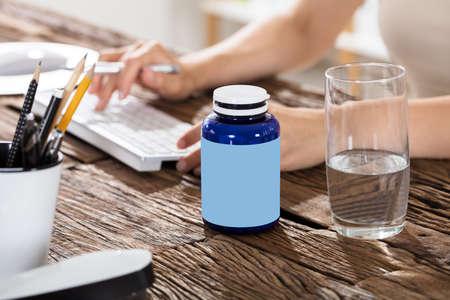 engrapadora: Drinking Glass Of Water With Pills Bottle On Wooden Desk Foto de archivo