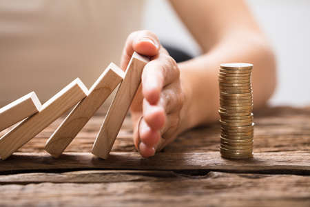 Close-up Of A Businesswoman's Hand Stopping The Wooden Blocks From Falling On Stacked Coins