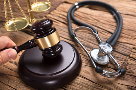 裁判官の法廷で木製のテーブルに聴診器と正義のスケールで木槌を打つ