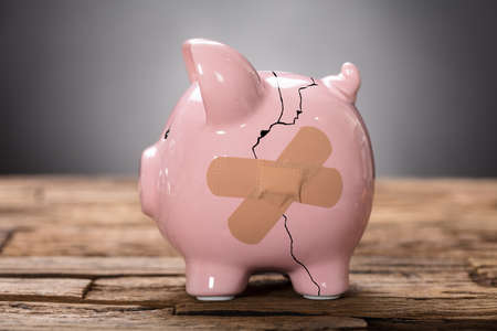 Closeup of broken pink piggybank with bandage on wood
