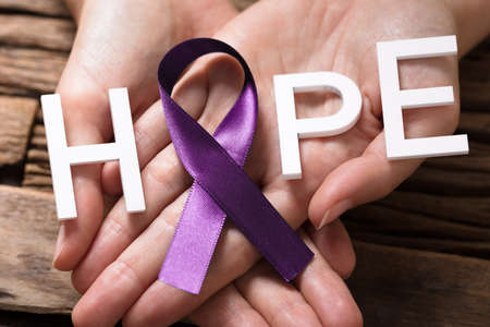 Close-up Of A Persons Hand Showing Ribbon With Hope Text To Support Alzheimers Disease Awareness