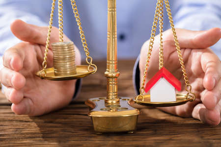 Close-up Of A Persons Hand Protecting Justice Scale With Stacked Coins And House Model Stock Photo