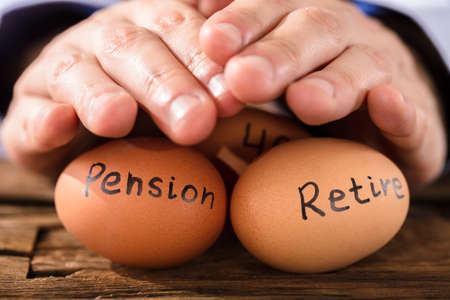 Close-up Of A Person's Hand Protecting Brown Egg Showing Pension And Retirement Text Archivio Fotografico