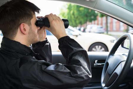 Primo piano di un uomo che si siede dentro l & # 39 ; automobile che osserva attraverso binoculare