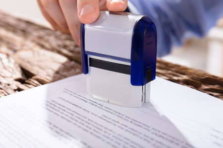 validation: Close-up Of A Persons Hand Stamping Document Over Wooden Desk