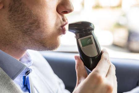 Primer plano de un hombre joven que se sienta dentro del coche que toma la prueba del alcohol