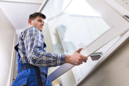 Low Angle View Of A Young Male Repairman Installing Window
