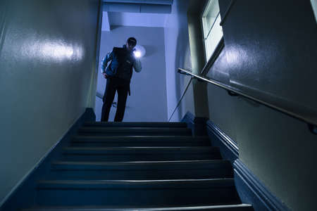 light duty: Male Security Guard Searching On Stairway With Flashlight Editorial