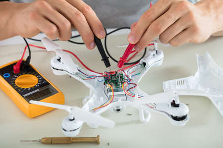 Close-up Of A Man Testing Electric Current Of Disassembled Drone Using Multimeter Tool