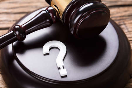 crime solving: Closeup of question mark and auction gavel