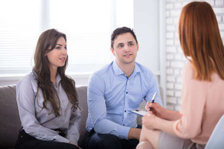 Young Couple Sitting With Psychologist In Office Redakční