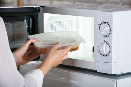 Close-up Of A Person Removing Prepared Food From Microwave Oven
