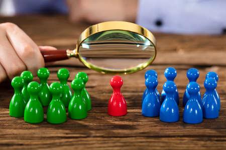 木製の机の上の虫眼鏡の数字を調べる人の手のクローズ アップ 写真素材
