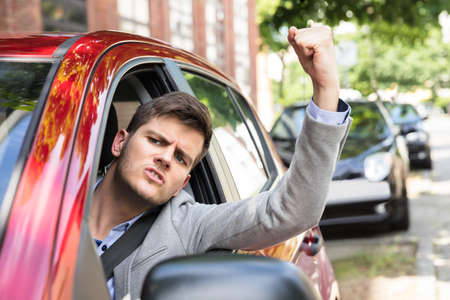 Close-up Of An Angry Man Looking Outside Car Window Stock Photo