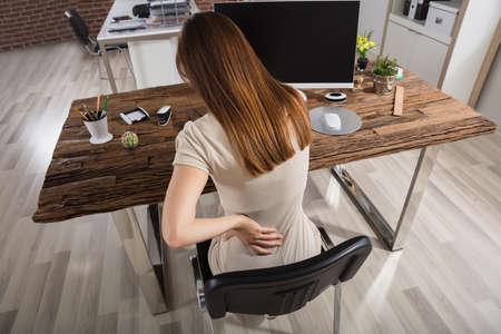직장에서 의자에 앉아 다시 고통을 데 젊은 사업가 스톡 콘텐츠