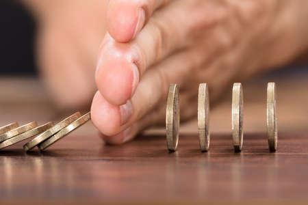 Bebouwd beeld van de hand die van de zakenman munten beschermen tegen het vallen terwijl het spelen van domino op lijst Stockfoto