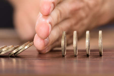 Cropped image of businessman's hand protecting coins from falling while playing domino on table Banque d'images