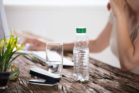 office stapler: Water Bottle And Drinking Glass On Desk And Woman In Foreground Using Computer