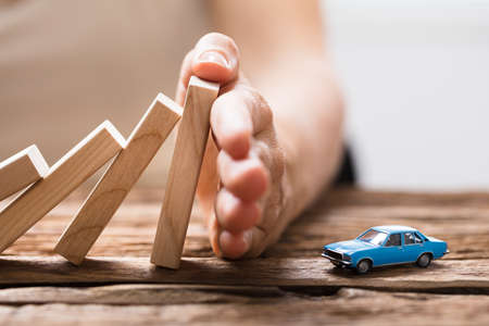 Close-up Of A Person's Hand Stopping The Wooden Blocks From Falling On Car Stock Photo - 84537749