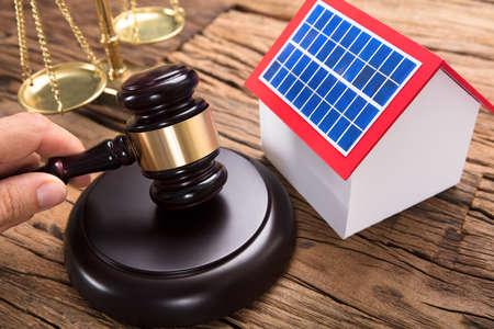 법정에서 나무 테이블에 태양 모델 집 및 정의 규모에 의해 망치를 타격하는 판사 스톡 콘텐츠