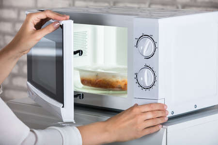 Womans Hands Closing Microwave Oven Door And Preparing Food At Home Stok Fotoğraf