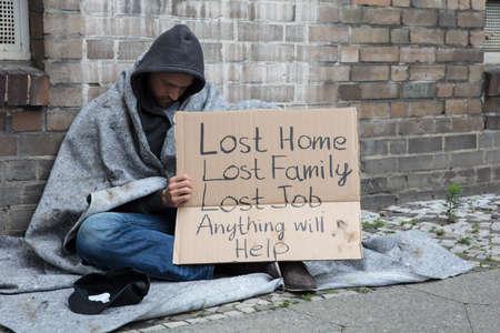 Homeless Man In Hood Sitting On Street Holding Cardboard Asking For Help