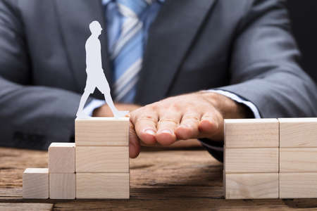 Midsection of businessman placing hand between wooden blocks with paperman walking on it photo