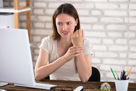 Young Businesswoman Holding Her Wrist At Workplace Stock Photo - 84270169