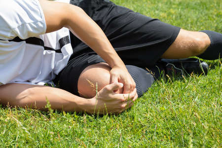 Close-up Of Male Player Suffering From Knee Injury Lying On Field